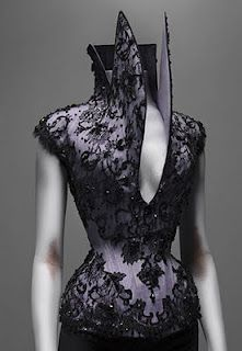 """Early in the exhibit, the Victorian and goth inspired collections utilize widows and mourners. In the Victorian era, each stage of mourning demanded a different color, one of which was lilac. The lilac repeats in future collections such as in fushia stocking in  the """"It's only a game"""" ensemble. Lilac stockings were also a hallmark of the House of Givenchy where McQueen worked before starting his own house. Givenchy continued to influence romantic softness of his work in future collections…"""