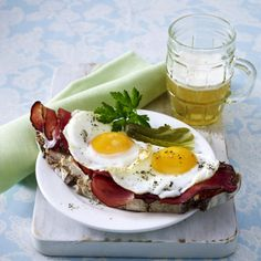 Strammer Max Rezept  6 TL   Butter   8   Eier (Größe M)      Salz      Pfeffer  4 Scheiben   Graubrot   4 Scheiben   roher geräucherter Schinken   2   Gewürzgurken       Petersilie