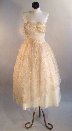 Classic 50s strapless dress with fitted waist & full below the knee skirt. Pictured with a petticoat ( sold separately) Designed in: 1950 Made of: tulle Color: ivory, gold Closure: side zip WAIST SIZE