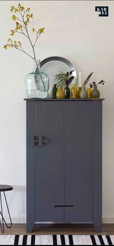Charcoal cabinet w earth tone vase collection, striped rug.