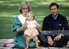 Sitting On A Rug With Her Husband, Prince Charles, Princess Diana Carefully Holds Prince William As He Tries Standing Up For His First Official Photocall During Their Tour Of New Zealand.