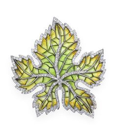 An art nouveau enamel and diamond maple leaf brooch, circa 1900 Set with plique-à-jour enamel ranging from green at the centre to brownish orange at the tips, the veins and border millegrain-set with rose-cut diamonds, mounted in platinum and gold, French assay mark, detachable brooch fitting, pendant loops on reverse, length 4.7cm