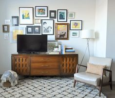 Beautiful mid-century modern credenza with original brass hardware, complimented by a colorful gallery wall.