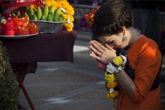 Beautiful colors and moment as a woman prays before participating in a celebration in Thailand.