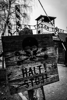 """The sign """"Halt"""" (Stop!) right behind (the picture is taken from inside the camp) the main gate to the camp with the 'Arbeit macht frei' inscription."""