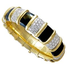 Designed as a black paillonné enamel hinged bangle, with alternating panels of black enamel and brilliant-cut diamonds, seperated by 18k gold vertical bands, all mounted in 18k yellow gold. Signed Tiffany & Co. by Jean Schlumberger