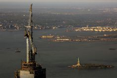 The spire for the top of One World Trade Center is hoisted into place at the top of the building in New York, on May 10, 2013. The State of Liberty is seen bottom right. (Photo: Gary He / Insider Images via EPA)