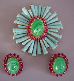 SCHREINER unsigned aqua  opaque ruffle rhinestones 3-1/8 by 2-7/8 brooch and 1-1/3 earrings with rosy  upside-down mounted rhinestone accents and marbled green  cabochons all set in gold tone, excellent condition, circa 1960s. Of all  the fabulous jewelry made by Schreiner, the ruffle motif is one of the  most popular and desirable designs.See other pieces in this series  in Carole Tanenbaum's Fabulous Fakes on page 122.