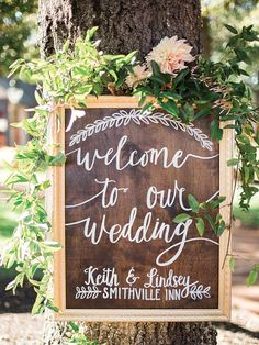 DIY a rustic wooden welcome sign with calligraphy for an outdoor wedding. Hang it up in a tree for guests to easily spot. Adorn the frame with florals for a gorgeous touch.