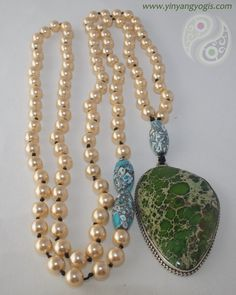 108 cream colored Swarovski Pearls made with mantra and intention enhanced by a Sterling Silver and rare Green Turquoise Pendant. The guru and accent beads are done in Blue Turquoise.