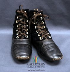 A pair of black leather and velvet child's boots. The boots are lace-up and the interior is made of white leather. Grey Roots Museum & Archives Collection.