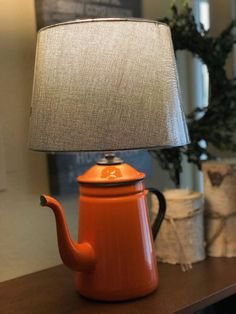 This is a beautiful antique enamel kettle that has been transformed into a lamp. Perfect for any tea lover or for your farmhouse kitchen. The tea kettle is orange with a black handle. Total lamp height is approximately 16 high. Lamp shade base is approximately 10 in diameter. Comes with Vintage Tea Kettle, Lampe Retro, Tea Pots, Enamel, Table Lamp, Farmhouse, Handle, Base, Lights