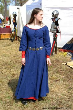 This is based on Waterhouse's paint­ing, Miranda — The Tem­pest. It is a blue cote­hardie with larger sleeves and a red under­dress. The but­tons are hand­made from the dress fab­ric.  Model: Daisy From http://www.faerie-queen.com/blue-cotehardie/