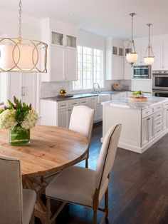 Cool white kitchen, with a stunning statuary white marble island. Table & chairs, light fixture. By Ellen Grasso & Sons. photography by Danny . Architectural design by Charles Isreal.
