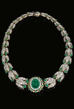 Emerald and diamond necklace, late 19th century. Set at the centre with a cabochon emerald bordered with circular-cut diamonds and kite-shaped emeralds, continuing to a series of graduated stylised lotus links set with rose, oval, single- and circular-cut, cushion and pear-shaped diamonds and circular-cut emeralds, length approximately 375mm.