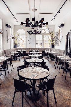 Morgan & Mees Restaurant interior, herringbone wood floor, white walls, black chairs, black lighting, taupe booth seating, sherwin williams poised taupe