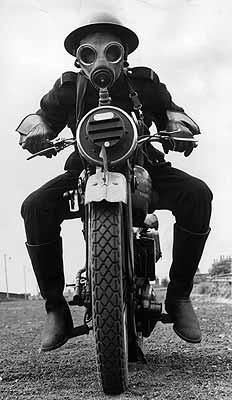 Man wearing gas mask on a motorbike.