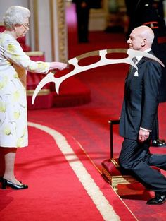 Sir Patrick Stewart. Her Majesty actually used a traditional sword; this was Photoshopped to add the bat'leff