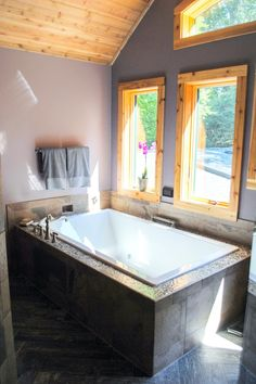 A luxurious two-person bathtub rests under a wall of windows in this rustic master bathroom. The beautiful wood-trimmed windows offer natural light and stunning views for a relaxing bathing experience.