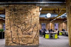 The new space features open workstations, graffiti, and common areas for the company's 100+ employees that work out of the company's home base.