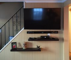 This is the after: larger TV, floating shelves, sound bar mounted on the wall