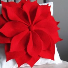 How to make an adorable poinsettia pillow out of felt pieces that's perfect for any time of the year (not JUST Christmas).http://www.billiemonster.com/blog/article/make-a-pretty-poinsettia-pillow-any-time-of-the-year