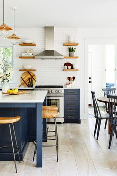 Anne had fond memories of the kitchen islands in the family's past summer rentals and wanted one of her own. Now they play cards and chat on West Elm stools .