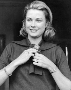 Princess Grace pinning a rose to her dress. August 28, 1963.