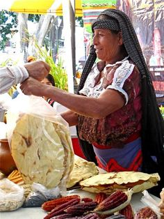 Market vendor in Oaxaca, Mexico selling tlayudas.  A tlayuda, a regional specialty, is a large sturdy tortilla that becomes an edible plate when spread with toppings.