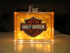 """Drill a 1"""" hole in the back of glass block. Stuff a 35-count white light string into block. Mask off the sides. Paint only front and back with orange glass paint. Use a credit card to spread it on nice and thick. Attach Harley sticker on front and a Harley toy on top."""