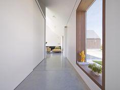 Puristischer Flur mit bodentiefen Fenstern und Boden aus Sichtestrich