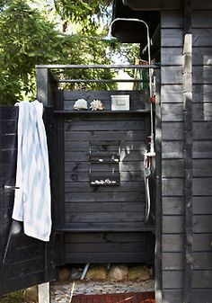 outdoor shower with exposed pipes, built-in wooden bench and wall soap dish