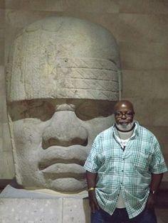 DR. RUNOKO RASHIDI WITH ONE OF THE OLMEC HEADS IN XALAPA, MEXICO