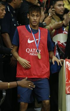 FC Barcelona's Neymar looks on after receiving souvenir trophy after their friendly soccer match in Shah Alam, Malaysia, Saturday, Aug. 10, 2013. FC Barcelona's won the match with score 3-1