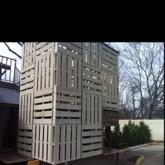 Innovative use of wood pallets to decorate exterior staircase. They could make an airy tree house too!