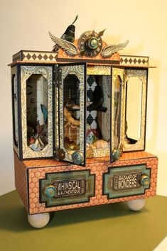 why not drawer pull as 'feet' for the boxes... and build on top of cigar box base... this looks like an old fashioned circus train car to me