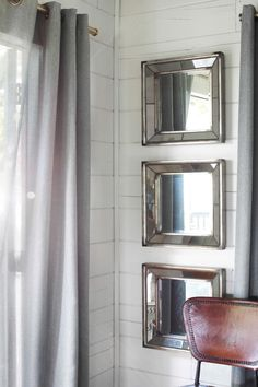 Three antiqued Uttermost Davion Squares Wall Mirrors were used to reflect light into an otherwise dark and shadowy corner.
