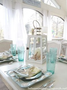 Beach Table Setting with Shell and Sailboat Plates.  A pretty Lighthouse Lantern with Shells as the centerpiece make this the perfect tablescape for summer from Between Naps on the Porch.