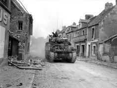 Sherman d'observation du 14e Régiment d'artillerie canadien entrant dans Caen par le quartier de la Maladrerie