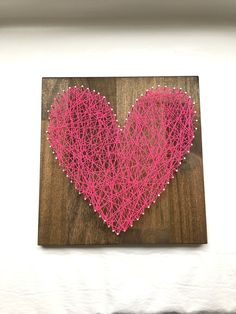 "Hot Pink Heart String Art - 12"" x 12"" - Nail and White String Art - Handmade - Ready to Ship - Ready to Hang with Hardware - Home Decor - Wall Art. This beautiful string art is made by me in my home. I start by milling the wood, sanding, then staining the wood. Once dried, I pick a pattern, pound the nails in and tie the string to make this amazing artwork. The popular wood is stained in dark walnut and measures approximately 12"" wide by 12"" tall by 2"" deep. This artwork is made in a…"