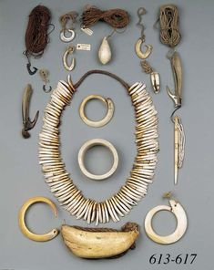 A collection of jewellery from Papua New Guinea, Pacific Bolas and 9 fishing hooks.  The necklace in the middle is a Asmat Tooth Necklace composed of 105 pig's teeth on plaited fiber.