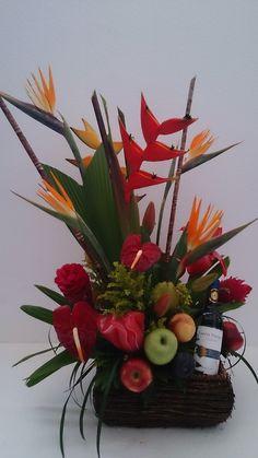 Arreglo de flores tropicales con frutas y vino