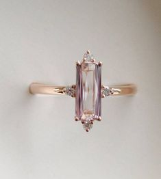 Baguette engagement ring by Eidelprecious. This beautiful and unique baguette engagement ring features a 1.25ct baguette cut Peach champagne sapphire set into 14k rose gold diamond setting. TDW 0.12ct, SI/I-J. The stone is sparkling and clean. Beautiful step cut. Sz 6, can be resized. #diamondsclean #cleandiamondsbeautiful