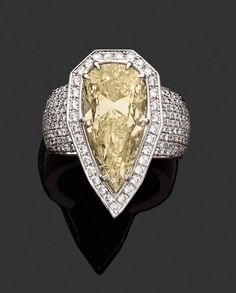 "Importante bague en or gris, ornée au centre d'un diamant poire de couleur ""Light Yellow"" entouré d'une ligne de petits diamants blancs, corps pavé de petits diamants blancs. Photo Tajan"