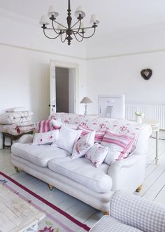 Very girly pink and white sitting room with lovely white linen sofa and vintage look cushions...