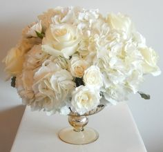 A more traditional wedding low centre-piece from Dizennio Floral Boutique-Vaughan , using ivory hydrangea, Polar Star roses and ivory Majollica spray roses.
