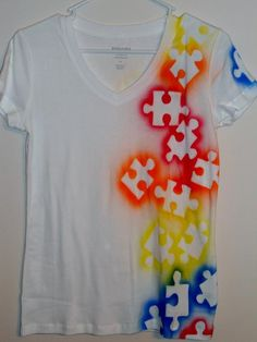 very easy to make ... puzzle shaped paper/cardboard cut + paint spray .. be careful to spray close to the edges of the paper cuts so it won't sprinkle all over the shirt
