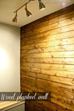 Wood Planked Wall-at the bottom of the stairs in the basement . Lights to highlight. Via: Thrifty Decor Chic