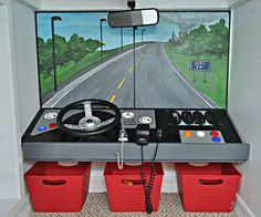 """The fire truck dashboard brings together assorted parts: a steering wheel (the kind used on playgrounds), an old CB radio, and a rearview mirror mounted to the ceiling. Corey painted a streetscape mural -- complete with smoke in the distance -- to provide a view through the """"window shield."""""""