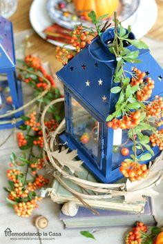 Fall/Thanksgiving table with old books, blue lanterns, orange cherries, mountain ash shrub, plaid napkins